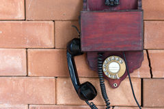 A vintage wooden telephone. Hanging on the brick wall Stock Photos