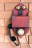 A vintage wooden telephone. Hanging on the brick wall Stock Photo