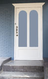 Vintage wooden white door in front of grey house Royalty Free Stock Photo