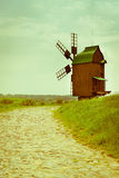 Vintage wooden windmill on stone road Stock Images