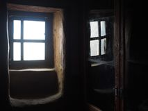 A vintage wooden window in a dark room, on the right is a reflection of a window in the glass. Royalty Free Stock Image