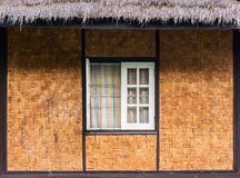 Vintage wooden window, twill weave wall and thatched roof Stock Photos