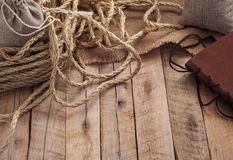 Vintage work table with rope, burlap sack and leather cover of book on plank wood surface Royalty Free Stock Photography