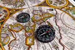 Vintage world map and compass. Contemporary compass on vintage world map. Selective focus Stock Images