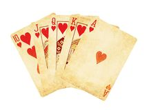 Vintage worn out hearts royal flush poker cards wooden table top. Vintage worn out hearts royal flush poker cards isolated on white Stock Photos