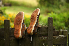 Vintage worn sneakers dried on a wooden fence Royalty Free Stock Photography