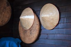 Vintage woven products bamboo wooden farmer hats and threshing basket or tray hanging on rustic wooden wall. Agricultural, Tradi royalty free stock photo