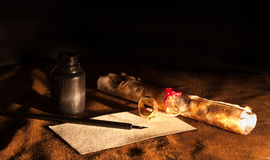 Vintage Writing Instruments. Close-up of a rolled envelope, paper, dip pen, inkwell Royalty Free Stock Photography