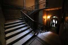 Vintage wrought iron staircase with wooden handrails and marble steps stock image