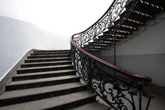 Vintage wrought iron staircase. With wooden handrails and steps royalty free stock image