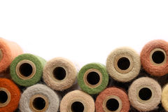 Vintage Yarn Spools Bordering White Background. A collection of natural colored antique yarn spools a framing a white background stock photography