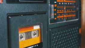 The Vintage Yellow Audio Cassette in the Old Tape Recorder Rotates. Macro static camera view of a vintage audio cassette tape with a blank label in use sound stock footage