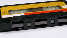 Vintage Yellow Audio Cassette Rotates on White Background. Retro tape cassette with a blank label. Old music. Close-up stock video