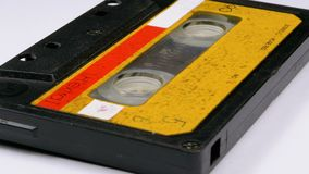 Vintage Yellow Audio Cassette Rotates on White Background. Retro tape cassette with a blank label. Old music. Close-up stock footage