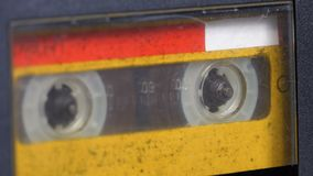 The vintage yellow audio cassette in the tape recorder rotates. Macro static camera view of a vintage audio cassette tape with a blank label in use sound stock video footage