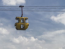 Vintage yellow cable car with blue sky background. It is a close up shot of a vintage yellow cable car with blue sky background Stock Photos