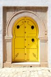 Vintage yellow door in Arabic style with a metal ornament. Royalty Free Stock Photo