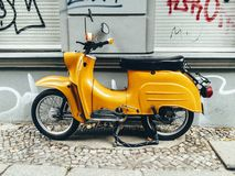 Vintage yellow motor scooter parked on footpath Royalty Free Stock Image