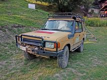 Old Landrover in rally version. Vintage yellow muddy four wheel drive Landrover in rally version parked on grass royalty free stock photography