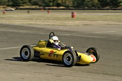 Vintage yellow racecar. Antique yellow racecar in the middle of a race stock photography