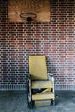 Vintage Yellow Reclining Wheelchair Under Basketball Hoop - Abandoned Hospital stock images