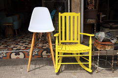 Vintage yellow rocking chair and lamp on flea market stock photography
