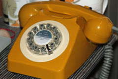 Vintage yellow telephone. Symbolizing retro fashion, modern technology as well as old fashioned technology Stock Photo