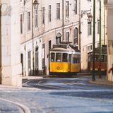 Vintage yellow tramway in Lisbon, Portugal. Bright tram on neutral background building. Tram edit up Royalty Free Stock Photography