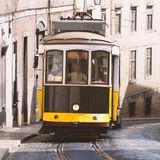 Vintage yellow tramway in Lisbon, Portugal. Bright tram on neutral background building. Tram edit up Royalty Free Stock Image