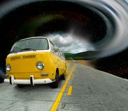 Vintage yellow van. A yellow vintage VW bus travels down an asphalt road out of a time warp with a road going into the distant mountains Stock Photo
