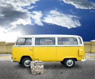 Vintage yellow van. A yellow volkswagen retro van.  The bus is on an asphalt street with retro luggage sitting beside the front door.  Concept for traveling Stock Photo