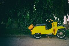 Vintage yellow Vespa parking The iconic Italian designed scooter. royalty free stock photos