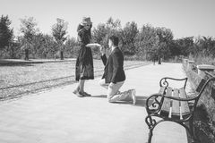 Vintage young man kneeling and asking a girl to marry him in the Stock Image