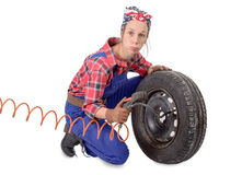 Vintage and young woman inflates a car tire Royalty Free Stock Photo