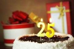 Vinte cinco anos de aniversário Bolo com velas e os presentes ardentes Fotos de Stock
