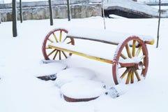 Vinter Den första snön har täckt den dekorativa bänken i parkera Fotografering för Bildbyråer