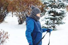 Vinter, fritid och underhållningbegrepp den gulliga unga pojken i lekar för blått omslag med snö, har gyckel, leenden Tonåringen  royaltyfri bild