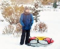 Vinter, fritid och underhållningbegrepp den gulliga unga pojken i lekar för blått omslag med snö, har gyckel, leenden Tonåringen  royaltyfria foton