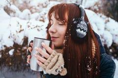 Vinter Kvinna med bärande öramuffs för rött hår Flicka som dricker den varma isolerade koppen för te eller för kaffe järn Fotografering för Bildbyråer