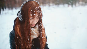 Vinter Kvinna med bärande öramuffs för rött hår Hon ser ner Snö på Arkivbild