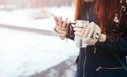 Vinter Kvinna med bärande handskar för rött hår Flicka som dricker den varma isolerade koppen för te eller för kaffe järn Det anv Royaltyfria Foton