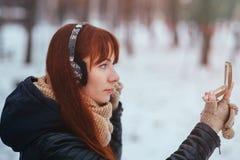Vinter Kvinna med rött hår som ser i spegeln på gatan Kvinnliga bärande öramuffs gör smink Arkivfoto