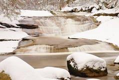 Vinter på bergfloden Stora stenar i strömmen som täckas med ny pulversnö och lat vatten med låga nivån Arkivbild