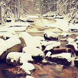 Vinter på bergfloden Stora stenar i strömmen som täckas med ny pulversnö och lat vatten med låga nivån Arkivfoto