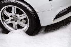 Vinter på vägen - framdelen av en vit bil med ett däck som parkeras i snön arkivbild
