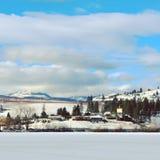 Vinter sjö, berg och stad Royaltyfri Bild