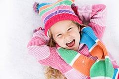 Vinter: Skratta lilla flickan som ligger i snö Arkivbild