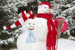 Vinter - snögubbe i ett snöig landskap med en hatt Arkivfoton