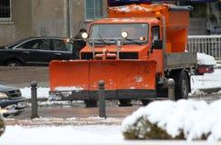 Vinter Snöplogen gör ren vägen i staden under en enorm snöstorm, snörengöringmaskin på boulevarden med bilar i stort snöfall royaltyfri bild