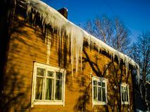 Vinter som ?r solig, sn?, istappar, hus, linje arkivfoto